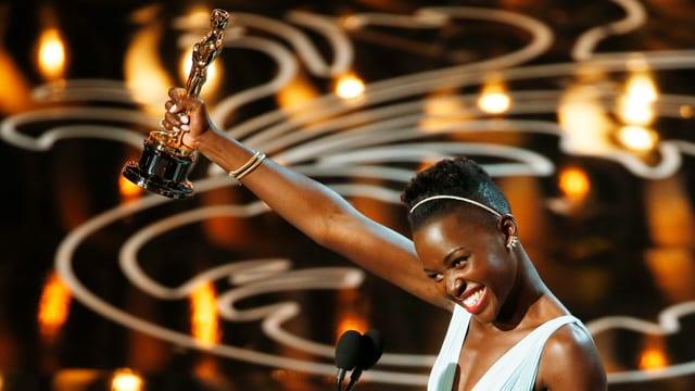 Lupita Nyong'o strahlt und hält den Oscar in die Luft.