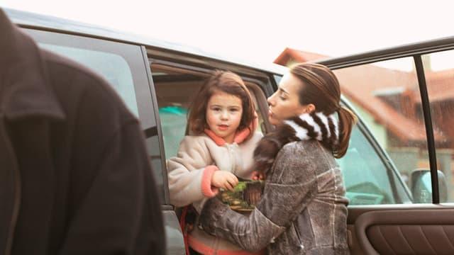Eine Mutter setzt ihr Schulkind ins Auto.