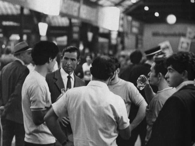 eine schwarz-weiss Fotografie von Männern in einer Bahnhofshalle
