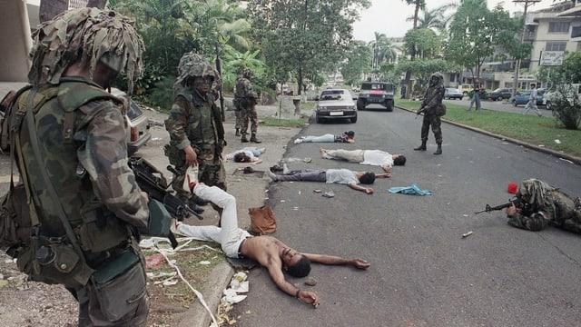US-Soldaten in Tarnanzügen in einer Strasse in Panama, Verdächtige Personen liegen am Boden.