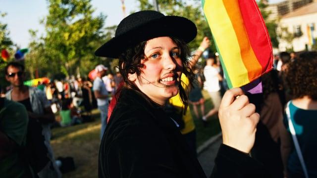Frau mit Regenbogenfahne.