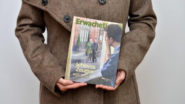 """Eine Frau hält ein Heft mit dem Titel  """"Erwachet!"""" in der Hand."""