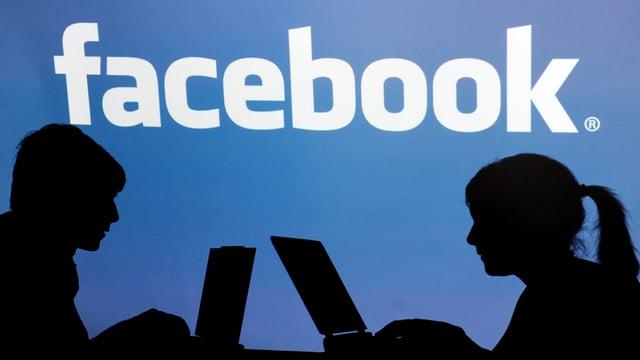 Silhouette von zwei Menschen mit aufgeklappten Notebooks, darüber das Facebook Logo.