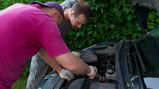 Zwei Männer betrachten den Motorraum eines älteren Autos.