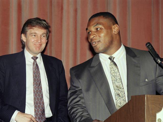 Mike Tyson steht an einem Rednerpult – dahinter ist Donald Trump zu sehen.