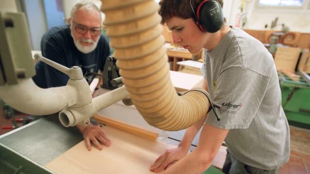 Ein Lehrling arbeitet unter Anleitung eines Lehrmeisters mit einer Kreissäge.