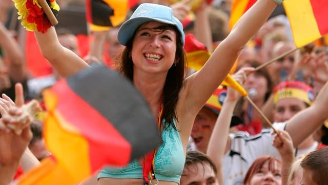 Ein weiblicher Fan jubelt. Im Hintergrund viele deutsche Flaggen.