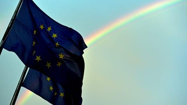 Zwei EU-Fahnen flattern im Wind. Im Hintergrund ein Regenbogen.