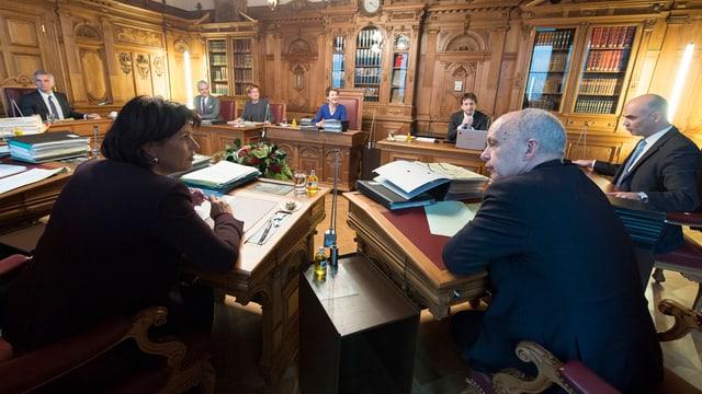 Die Bundesratmitglieder sitzen an Pulten im Kreis.