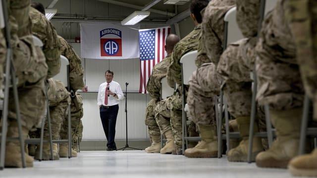 Soldaten sitzen in einer Halle auf Stühlen, vor ihnen spricht ein zivil gekleideter Mann.