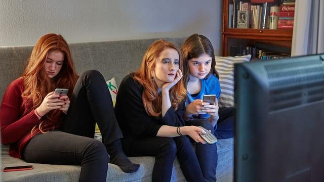 Symbolbild: Vier jugendliche Mädchen vor einem TV-Bildschirm, zwei von ihnen hantieren am Handy.