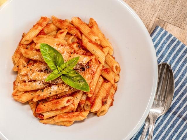 Ein Teller mit Penne an Tomatensauce.