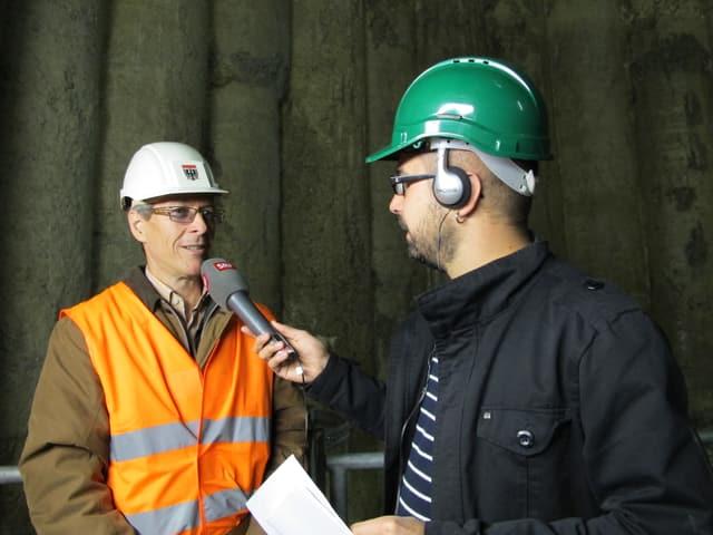 Schüttel trägt ein orange Weste und einen weissen Bauhelm, Alagheband trägt einen grünen Helm und hat ein Mikrofon in der Hand.