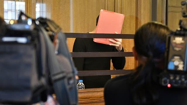 Angeklagter verdeckt Gesicht mit Mappe.
