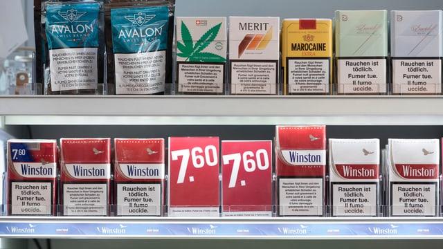 Zigarettengestell mit Päckchen diverser Marken, darunter auch eine Packung Hanfzigis.