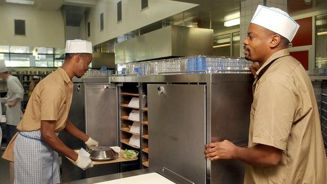 Kongolese mit einem Küchenschurz hat ein Tablett mit Essen in der Hand. Ein anderer Mann steht daneben.