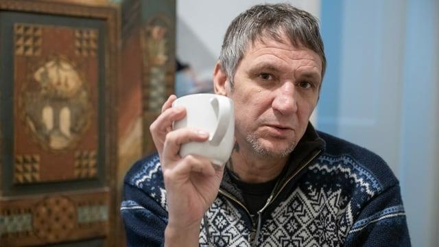Ein Mann im Norweger-Pullover hält eine Kaffeetasse in der Hand und blick tin die Kamera.
