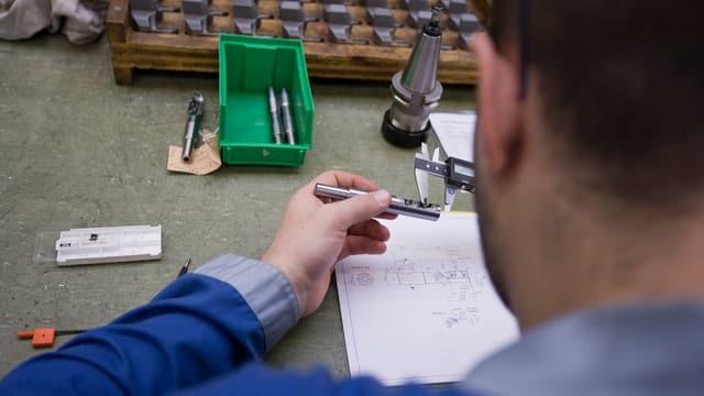 Ein Mitarbeiter des Schweizer Werkzeugherstellers Urma AG arbeitet in Rupperswil im Kanton Aargau an einem Maschinenteil.