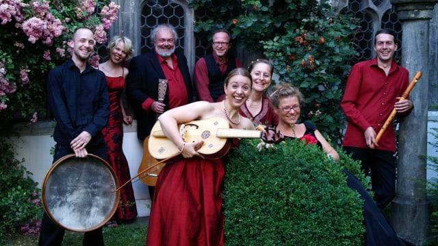 Das Ensemble steht in einem Garten, alle rot-schwarz gekleidet.