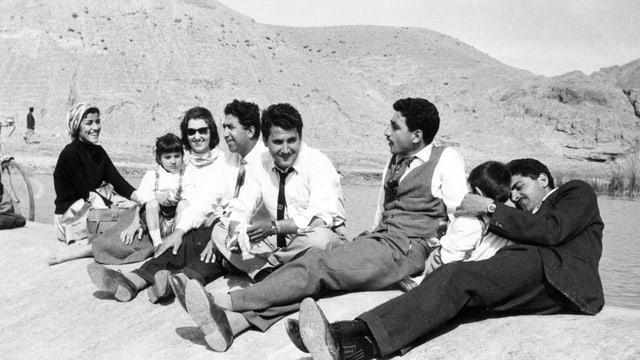 Schwarzweiss-Foto einer gruppe Menschen, die im Freien auf dem Boden sitzt.