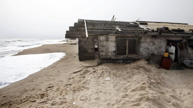 Das Haus ist bis zur Hälfte im Sand eingesunken und die Wellen kommen schon bedrohlich nahe.