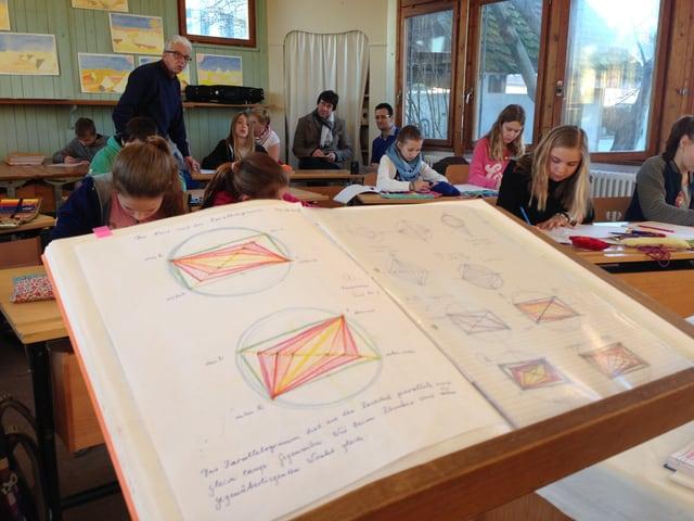 Vorne liegt das aufgeschlagene Buch des Lehrers mit den Skizzen, im Hintergrund sieht man die Schüler.