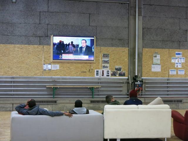 Asylbewerber sitzen ausf Sofa und schauen fern.