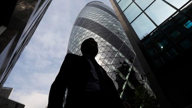 """Ein Mann im Anzug geht vor dem Swiss Re-Gebäude in London vorbei, das als """" the Gherkin"""" bekannt ist."""