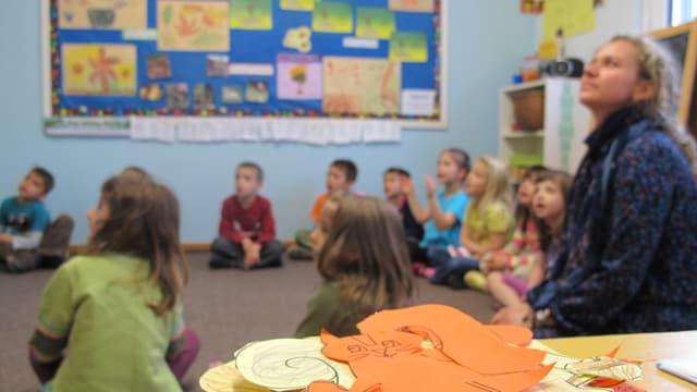 Eine Lehrerin sitzt mit Kindern in einem Schulzimmer.