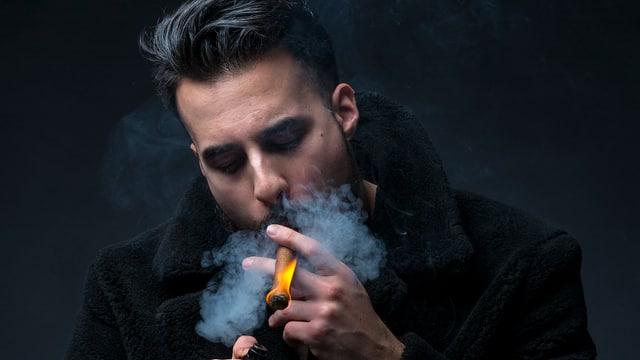 Der Rapper Don Fuego entzündet eine Zigarre
