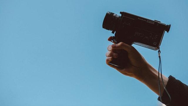 Eine Person hält eine Super 8 Videokamera in den blauen Himmel.