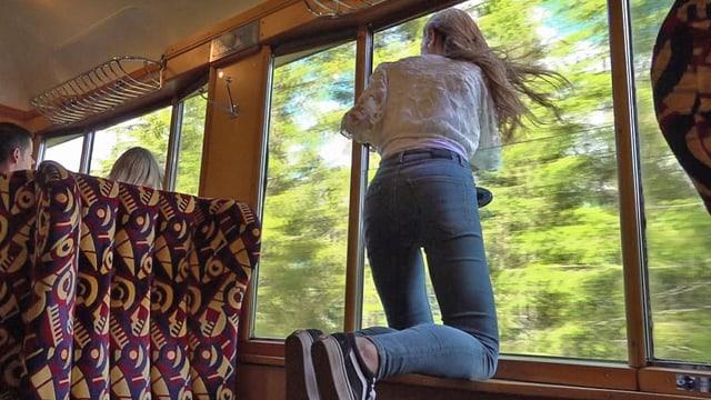 Influencerin kniet auf einem Zugtischchen und lehnt sich aus dem Fenster.