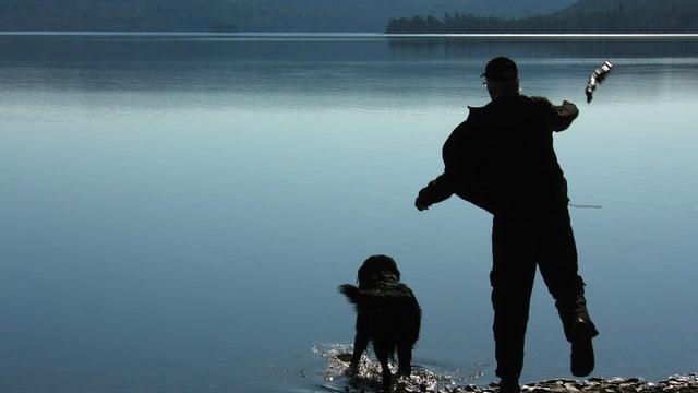 Ein Mann an einem See wirft einen Stock, damit sein Hund ihn wieder holen kann.
