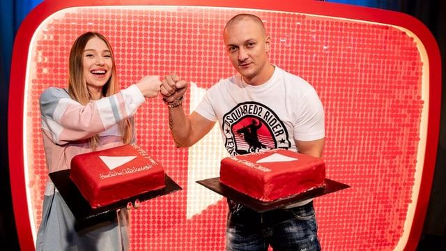 """Eine junge Frau und ein junger Mann stehen vor einem grossen roten """"YouTube""""-Logo auf einer Bühne"""