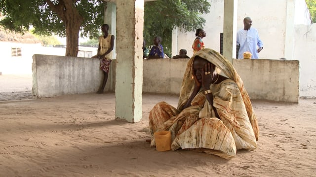 Eine Frau in afrikanischer Kleidung sitzt mit Händen vor dem Gesicht auf sandigem Boden.