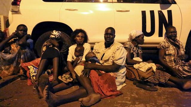Flüchtlinge rasten vor einem Uno-Fahrzeug