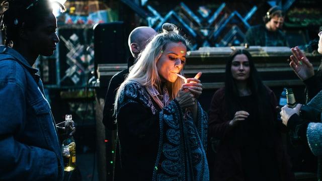 Eine junge Frau zündet sich an einer Party eine Zigarette an.