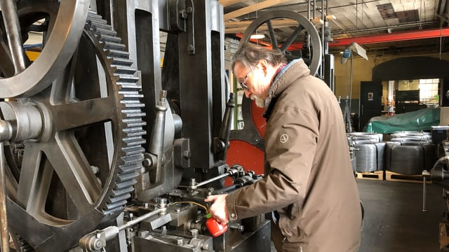 Ein Mann mit einem Ölfläschen giesst Öl in eine Maschine.