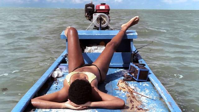 Eine Frau liegt im Bikini auf einem blauen Holzboot.