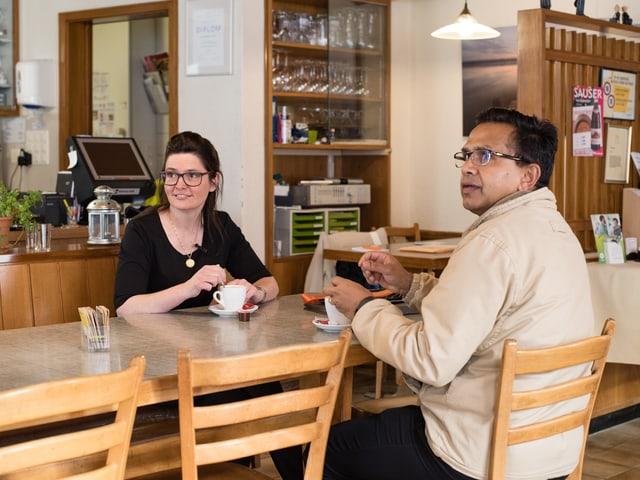 Prasad Bharanya und Jeannine Schilder stizen am Tisch.