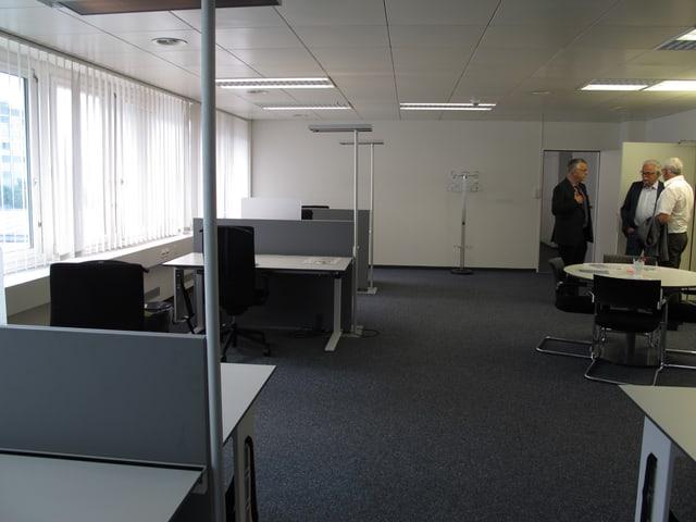 Blick in Grossraumbüro mit Arbeitsplätzen und drei Männern im Gespräch.