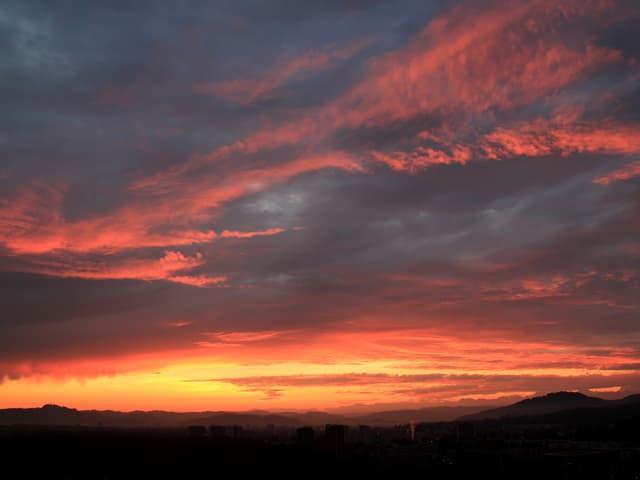 Rot gefärbte Wolken am Morgenhimmel. Stadt noch im dunkeln.