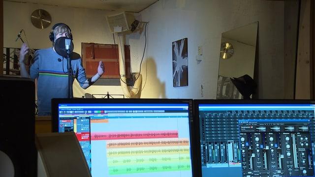 Massai am Mikrofon am singen, im Vordergrund sind zwei Computerbildschirme.