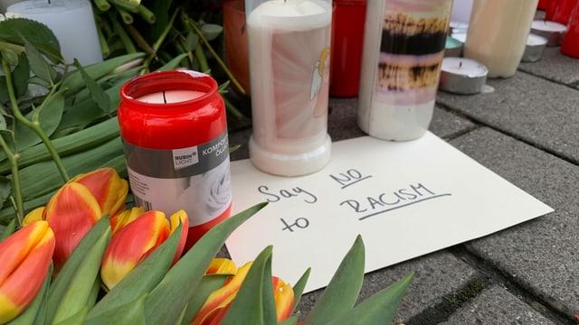 «Say No to Racism»-Schild, daneben Blumen und Kerzen