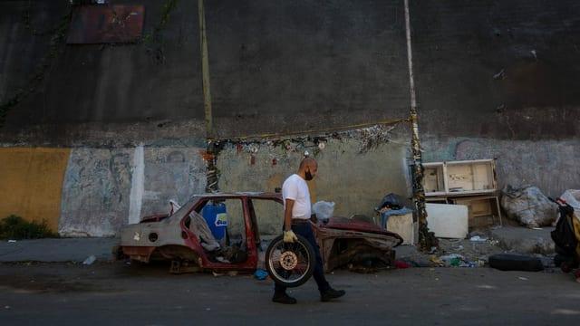 Mann schleppt Rad in Armenviertel von Caracas, Februar 2021