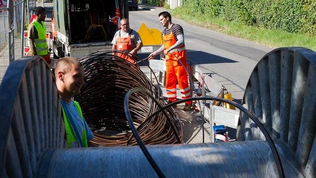 Arbeiter ziehen Glasfaserkabel in bestehende Rohre ein.