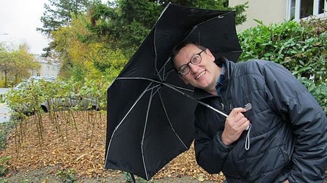 Mann mit Brille hält einen schwarzen Regenschirm und lacht in die Kamera.