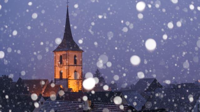 Schneeflocken vor der nächtlichen Kirche in Muttenz.