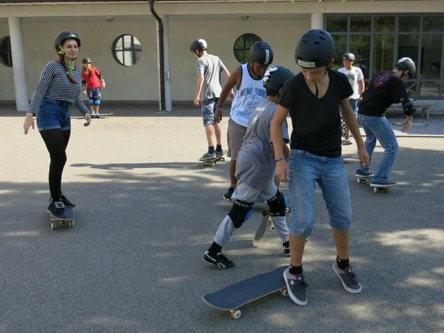 Jugendliche auf einem Pausenplatz mit Skateboards.