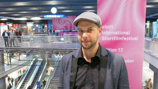 Olivier van der Hoeven vor dem Festival-Plakat im Berner Bahnhof.